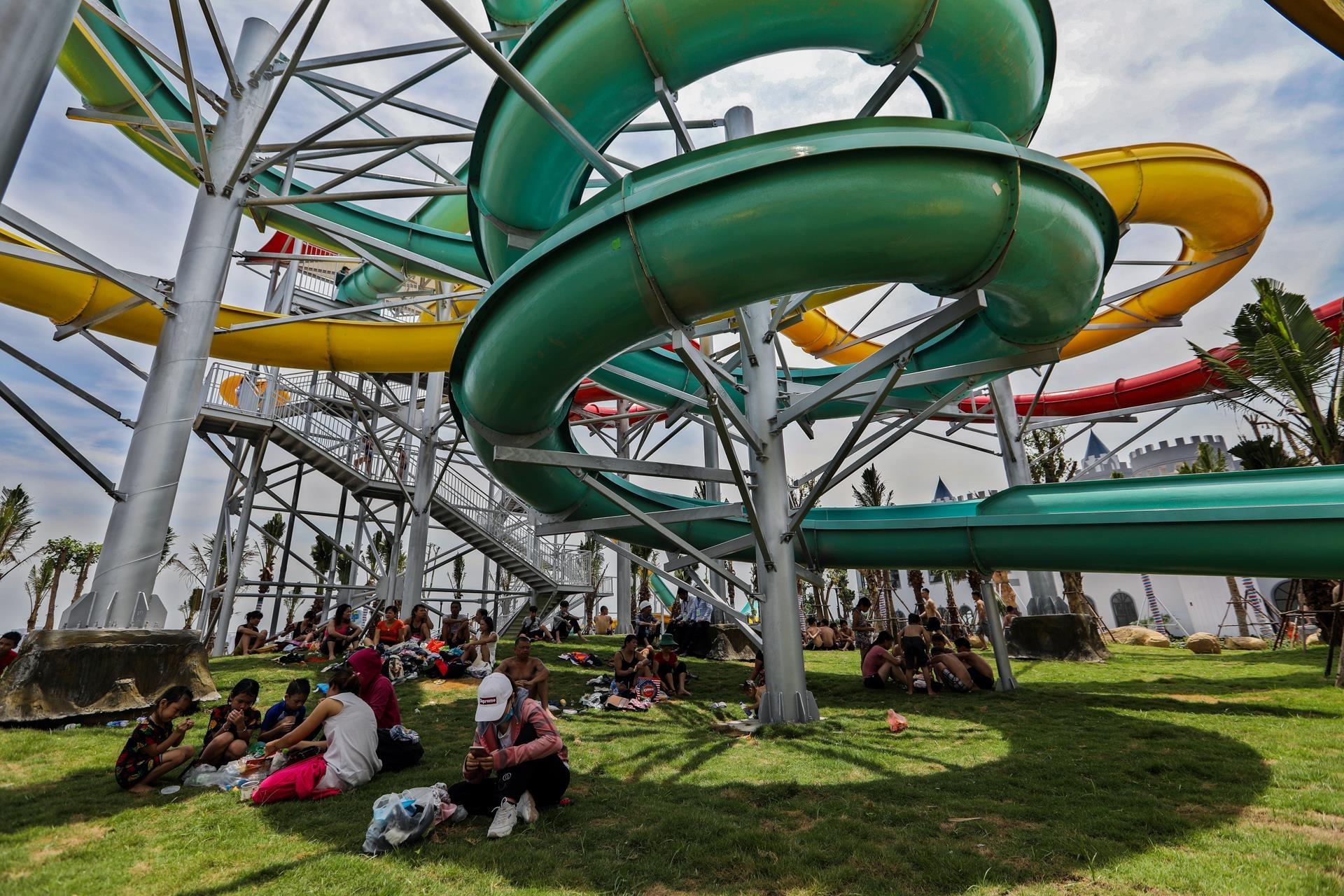 Du khách phải tìm chỗ nghỉ ngơi tránh nắng dưới bóng mát của những máng trượt khổng lồ.