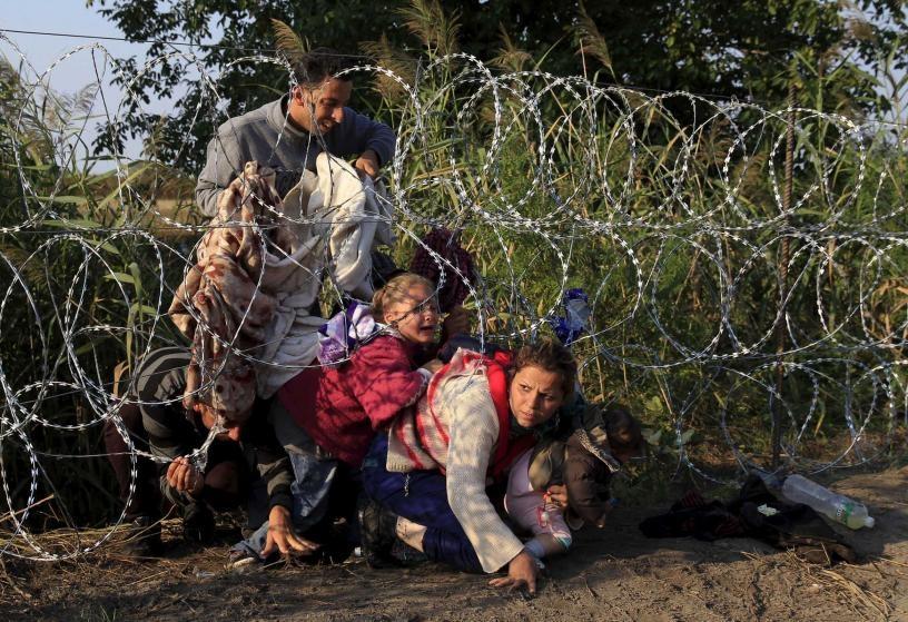 Chu tich FIFA duoi con mua tien vao top anh noi bat cua TIME hinh anh 8 Người tị nạn Syria cố gắng chui qua hàng rào thép gai để vào Hungary tại biên giới giáp Serbia ngày 27/8.