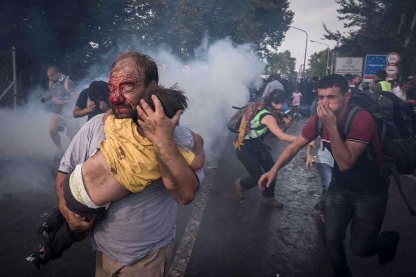 Chu tich FIFA duoi con mua tien vao top anh noi bat cua TIME hinh anh 10 Một người đàn ông nhập cư bế em nhỏ trong vụ đụng độ với cảnh sát chống bạo động Hungary tại biên giới gần thị trấn Horgos của Siberia ngày 16/9. Giới chức Hungary quyết định đóng cửa biên giới sau khi làn sóng người tị nạn tràn qua nước này với số lượng rất lớn.