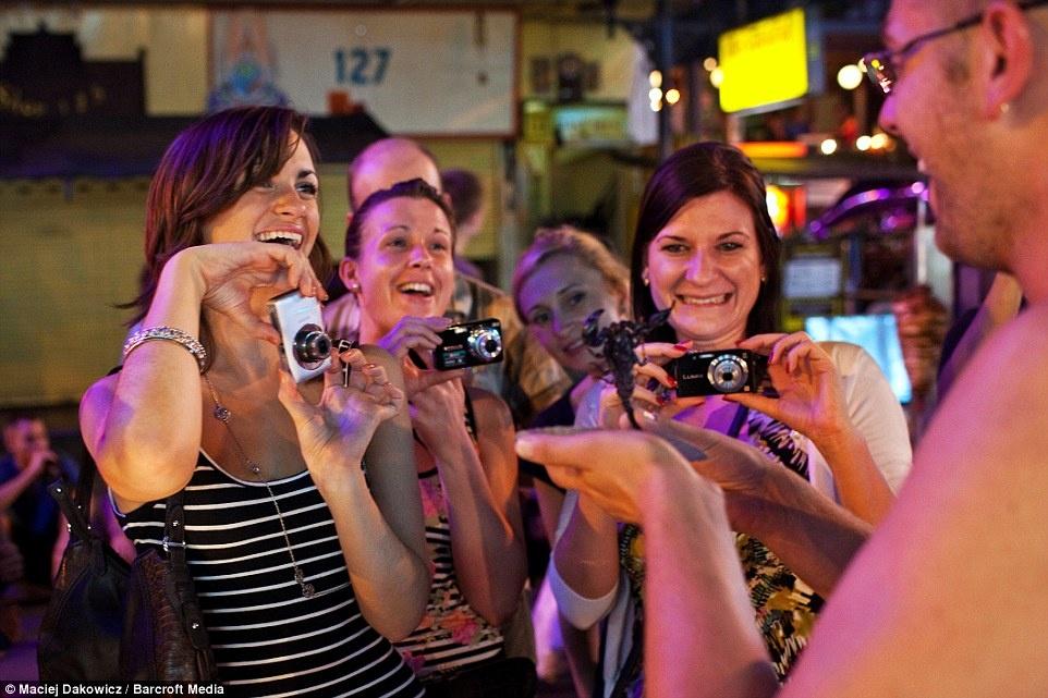 Cuoc song soi dong ve dem o pho Tay Bangkok hinh anh 22 Nhóm du khách phương Tây đồng loạt ghi lại hình ảnh bọ cạp trong tay người bán hàng.