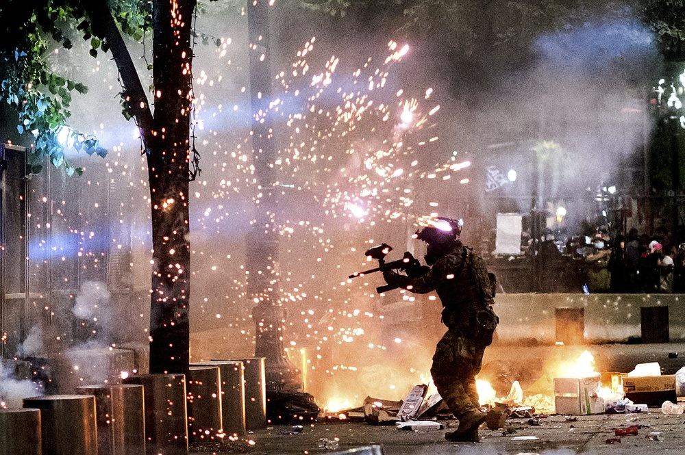 Cứ mỗi lần hơi cay tan đi, người biểu tình lại tập trung trở lại thành từng nhóm, hô khẩu hiệu và rung hàng rào bao quanh tòa án liên bang, thứ ngăn cách giữa họ và lực lượng chấp pháp. Vẫn chưa có thông tin chính thức về số vụ bắt giữ trong đêm 24/7. Ảnh: AP.