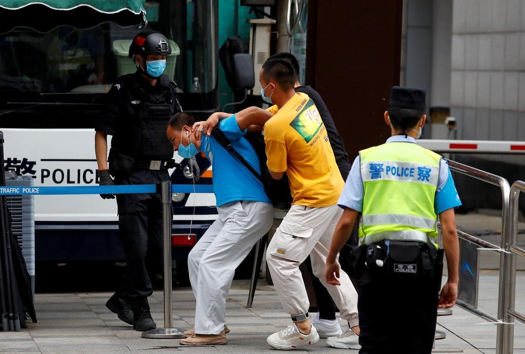 Nhân viên an ninh mặc thường phục bắt giữ một người đàn ông mang theo biểu ngữ đứng bên ngoài lãnh sự quán Mỹ ở Thành Đô sáng 25/7. Ảnh: Reuters.