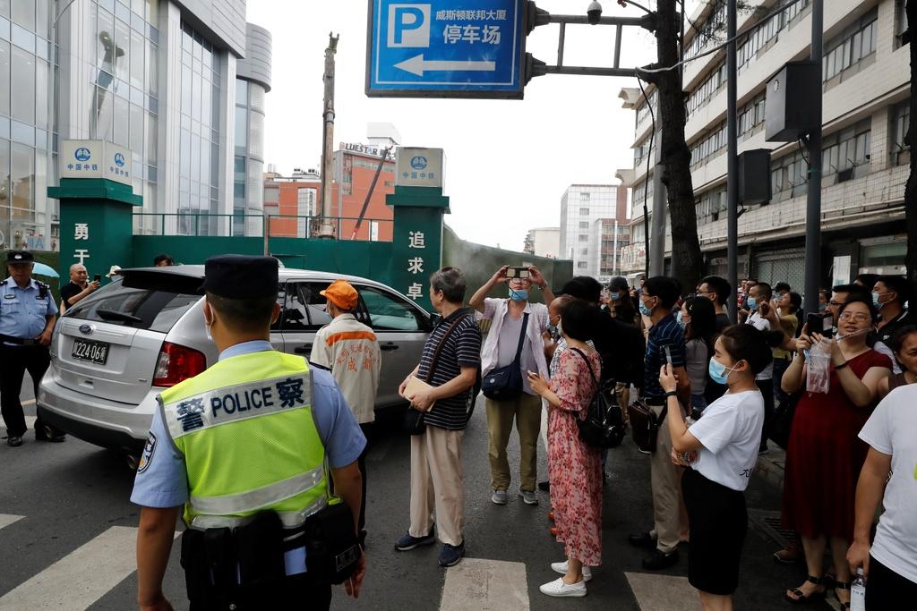 Người dân vẫn di chuyển phía bên kia đường trong ngày. Một số người chụp vội hình ảnh hoặc quay phim tòa nhà trước khi bị cảnh sát yêu cầu rời đi. Ảnh: Reuters.
