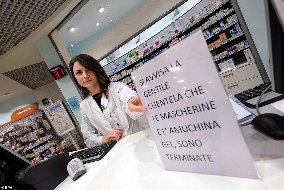 Ben trong nhung sieu thi, cua hang Italy mua dich Covid-19 hinh anh 5 25162606_8041467_An_employee_shows_a_sign_informing_customers_that_the_disinfecta_a_3_1582627652640.jpg
