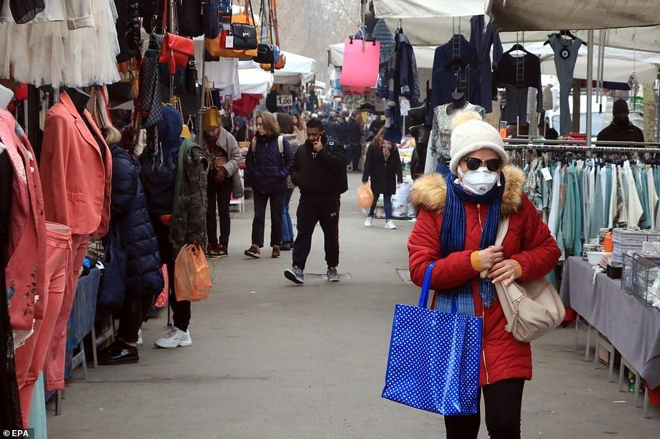 Ben trong nhung sieu thi, cua hang Italy mua dich Covid-19 hinh anh 8 25169178_8041467_A_woman_wearing_a_face_mask_walks_among_stalls_at_street_market_a_6_1582661175026.jpg
