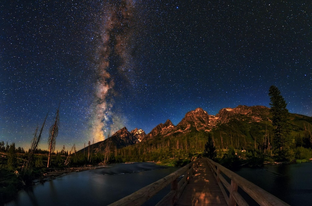 """Dải sao sắc màu """"đổ"""" xuống dãy núi Rocky ở công viên Quốc gia Grand Teton (Mỹ) như mở ra một con đường bí mật đi vào vũ trụ. Thực chất, đây là dải ngân hà kéo dài từ chòm sao Tiên Hậu (Cassiopeia) ở phía bắc đến chòm sao Nam Thập Tự (Crux) phía nam đất nước này. Ảnh chụp của nhiếp ảnh gia Babak Tafreshi trong một lần ghé thăm dãy núi hùng vĩ của Mỹ."""