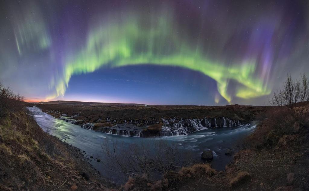 Cực quang là hiện tượng quang học được hình thành do sự tương tác của các hạt mang điện tích từ gió Mặt Trời với tầng khí quyển. Các dải cực quang liên tục chuyển động khiến người xem có cảm giác như dải lụa vắt ngang trời. Hình ảnh bầu trời đầy sao ẩn mình sau dải cực quang   trên thác nước dọc theo sông Hvita (Iceland) được nhiếp ảnh gia người Iran Babak Amin Tafreshi ghi lại.
