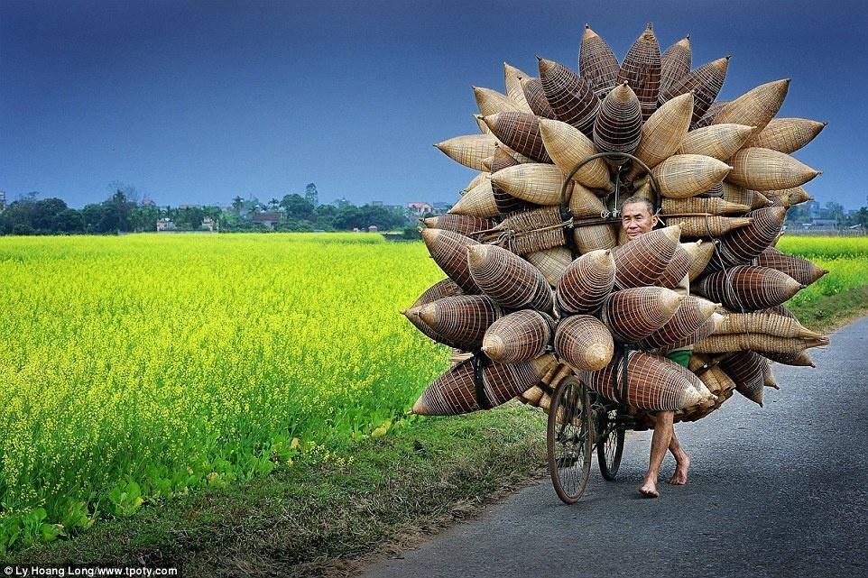 """Giải """"Nhiếp ảnh gia du lịch của năm"""" 2015 có sự tham gia của nhiều thí sinh tới từ 22 quốc gia, với giám khảo là những tên tuổi uy tín trong ngành. Trong đó, bức ảnh chụp một lão nông đang dắt xe chở đó ở làng Tất Viên, tỉnh Hưng Yên, Việt Nam, của tác giả Lý Hoàng Long đã nhận được nhiều khen ngợi ở hạng mục Khuôn mặt, con người, gặp gỡ."""