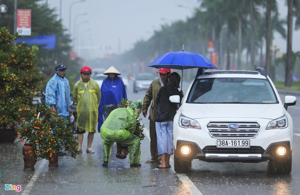 Người bán hoa Tết co ro ngóng khách trong cơn mưa tầm tã