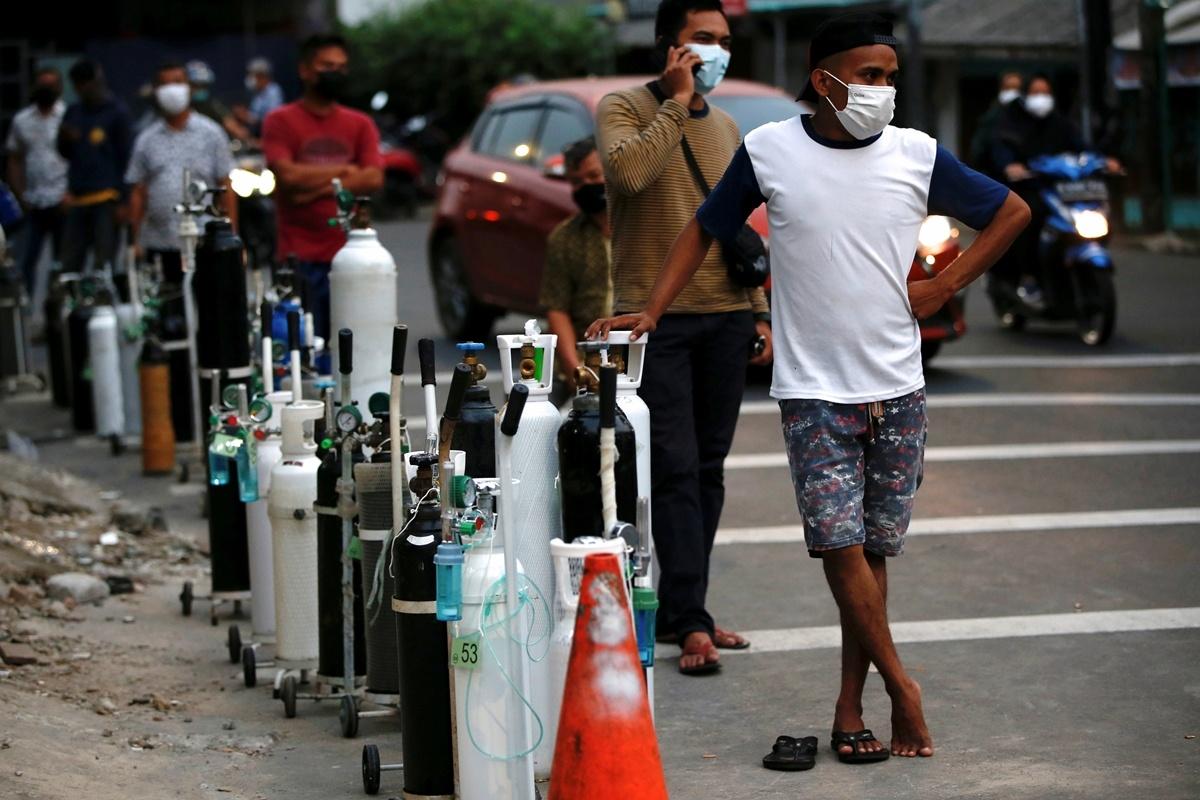 Người dân xếp hàng chờ tới lượt bơm đầy bình oxy y tế cho người nhà mắc Covid-19 tại Indonesia. Ảnh: Reuters.