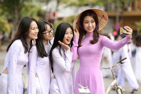 Hoa hau My Linh noi bat voi ao dai tim va non la tren pho Nguyen Hue hinh anh 9