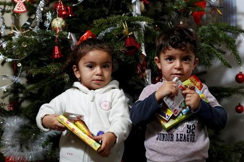 Sac vang, trang, do tran ngap the gioi dip Giang sinh hinh anh 13 Cặp song sinh Hevedar và Heve (trái) người Iraq được nhận quà dịp Giáng sinh trong một khu tị nạn ở Đức. Ảnh: Reuters