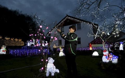 Sac vang, trang, do tran ngap the gioi dip Giang sinh hinh anh 15 Một phụ nữ điều chỉnh ánh sáng trang trí Giáng sinh bên ngoài ngôi nhà của cô ở thị trấnBenesov nad Ploucnici, Cộng hòa Czech