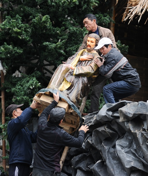 Cac nha tho chuan bi don Giang sinh hinh anh 3 Tại nhà thờ Lớn Hà Nội, các giáo dân đang vận chuyển các bức tượng vào vị trí để tái hiện cảnh chúa Giêsu ra đời.