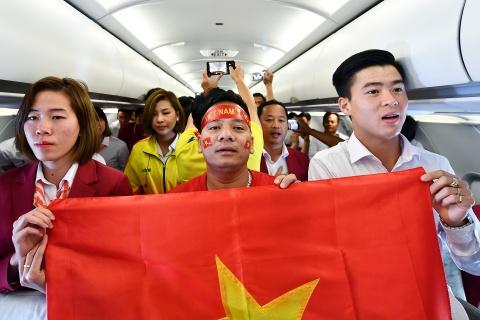 Cau thu doi Olympic Viet Nam hat Quoc ca tren may bay hinh anh