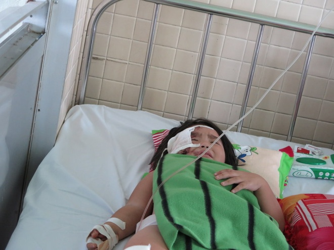 Bé Thùy Vân đau đớn do bị kính cứa vào mặt sau tiếng nổ sập nhà.