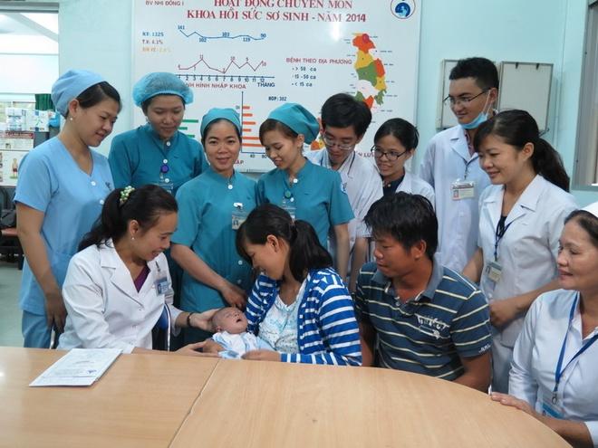 Các y bác sĩ đón tiếp bé Phát tái khám tại khoa Hồi sức sơ sinh. Ảnh: Khánh Trung.
