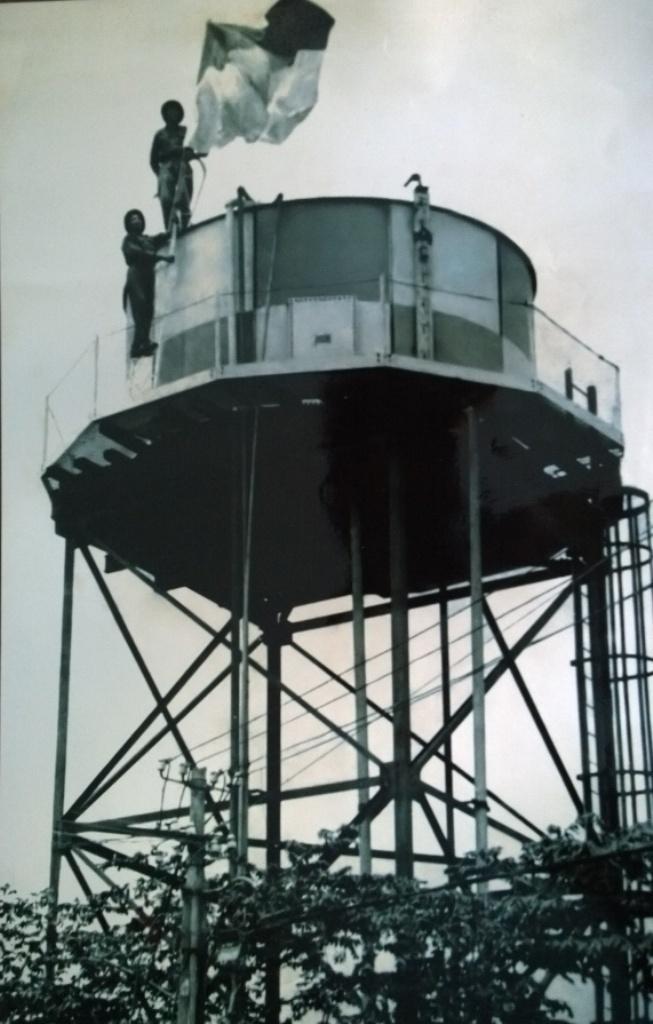 Nguoi cam co giai phong sang 30/4 tai Sai Gon hinh anh 3 Ông Cẩn (người đứng dưới) cùng đồng đội cắm cờ giải phóng ở tháp nước sân bay Tân Sơn Nhất. Ảnh: NVCC.