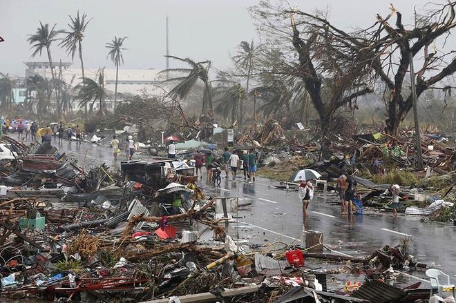 Nhung canh bao dang so ve bien doi khi hau (ky 2) hinh anh 5 Người dân di chuyển trên một con đường ngập đổ nát sau khi siêu bão Haiyan đổ bộ vào thành phố Tacloban, miền trung Philippines, hồi tháng 11/2013. Hơn 10.000 thiệt mạng sau cơn bão được cho là mạnh nhất trong lịch sử theo nhận định của các chuyên gia.