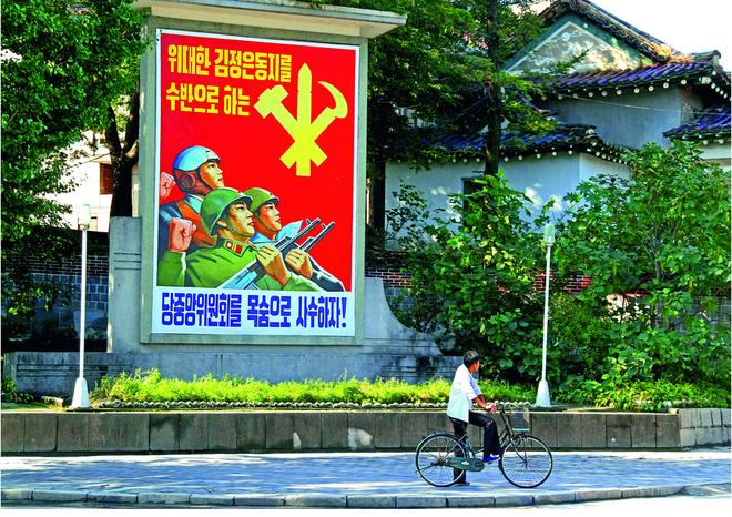 Một người đàn ông đi xe đạp ngang qua tấm áp phích tại khu công nghiệp Kaesong, nằm cách biên giới hai nước khoảng 9, 5 km.