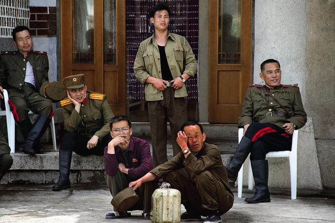 Một nhóm đàn ông Triều Tiên ngồi trước cửa khách sạn Dân tộc Minsok ở thành phố Kaesong.