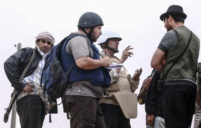 Nghi van ve thoi diem phien quan sat hai nha bao Sotloff hinh anh 2 Nhà báo Steven Sotloff (áo khoác xanh) trao đổi với phe nổi dậy Libya vào tháng 6/2011. Ảnh: AFP