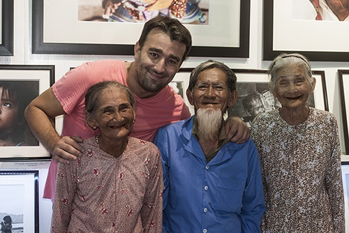 Anh chan dung nguoi Viet an tuong tren bao nuoc ngoai hinh anh 10 Nhiếp ảnh gia Réhahn Croquevielle bên gia đình ông bà Lê Văn Sẻ (91 tuổi) và bà Nguyễn Thị Lợi (83 tuổi, ngoài cùng bên phải) tại gallery tranh của Réhahn. Hai cụ sống đã gắn bó với nhau từ khi mới hơn 20 tuổi, sống chung 63 năm ở làng Trà Quế, cách thị trấn Hội An 3km. Ảnh: NVCC