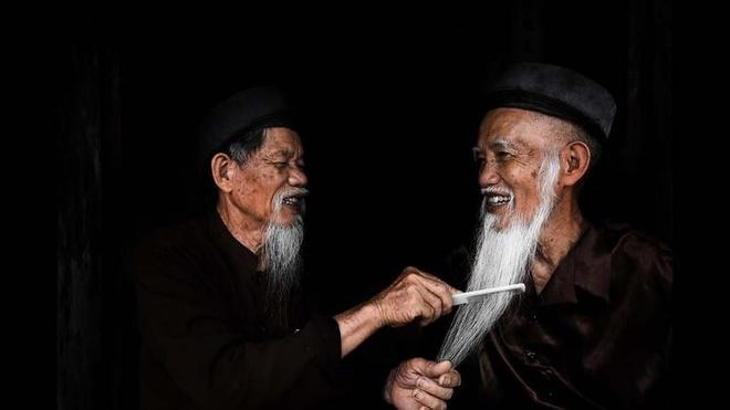 Anh chan dung nguoi Viet an tuong tren bao nuoc ngoai hinh anh 8 Hai ông cụ, vốn là hai anh em, sống tại Tam Cốc, Ninh Bình, chải râu cho nhau. Người em tên Chu Van Thim (76 tuổi) và người anh tên Chu Van Nhan (83 tuổi). Ảnh: LA Times