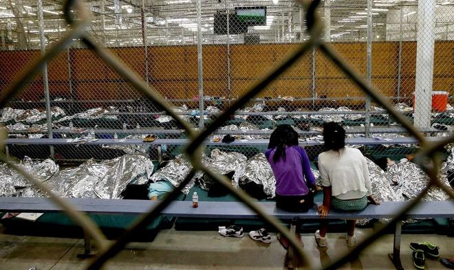 Obama om y ta goc Viet la khoanh khac an tuong 2014 cua My hinh anh 4 Khủng hoảng nhập cư của Mỹ: Hai cô gái theo dõi một trận đá banh từ một trung tâm tạm trú tại Nogales, bang Arizona. Đây cũng là nơi hàng trăm trẻ em Trung Mỹ đang chờ được Cơ quan hải quan và bảo vệ biên giới làm thủ tục xét duyệt hồ sơ nhập cảnh. Hơn 47.000 trẻ em không đi cùng cha mẹ đã vượt biên trái phép vào Mỹ. Ảnh: AP