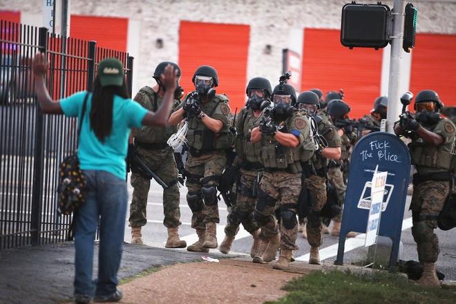 Obama om y ta goc Viet la khoanh khac an tuong 2014 cua My hinh anh 6 Cảnh sát chống bạo động hướng về phía một người đàn ông tham gia cuộc biểu tình ở Ferguson, Missouri, tháng 8/2014. Những cuộc biểu tình phản đối phán quyết của tòa án vì không khép tội viên cảnh sát bắn chết một thanh niên da màu đã bùng phát thành làn sóng bạo lực nghiêm trọng suốt những tháng qua ở Mỹ. Ảnh: AP
