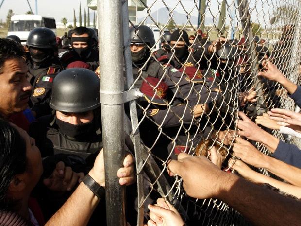 Nhung vu tham sat tu nhan kinh hoang trong trai giam hinh anh 5 Cảnh sát ngăn cản cuộc biểu tình của gia đình tù nhân thiệt mạng trong cuộc ẩu đả giữa hai băng nhóm ở nhà tù tại Mexico năm 2012. Ảnh: AFP