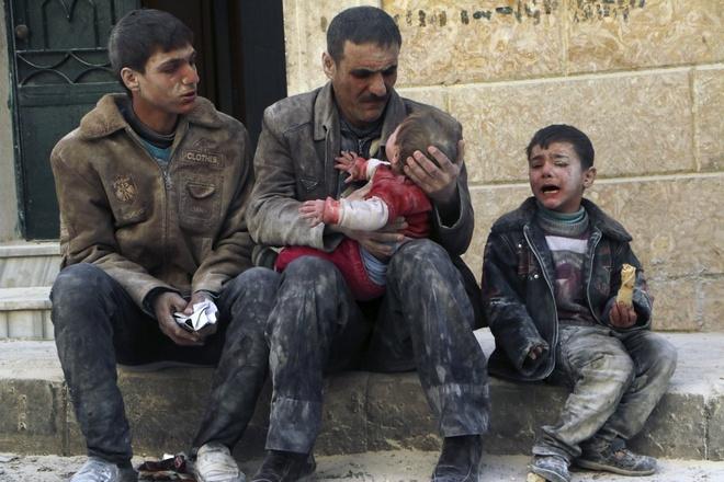 Cuộc nội chiến đẫm máu tại Syria vẫn tiếp diễn trong năm qua. Trong ảnh là người đàn ông ôm một đứa bé được cứu sống khỏi đống đổ nát ở thành phố Aleppo hồi tháng 2. Sự việc xảy ra sau khi lực lượng trung thành với Tổng thống Bashar Assad thực hiện một vụ không kích vào thành phố.