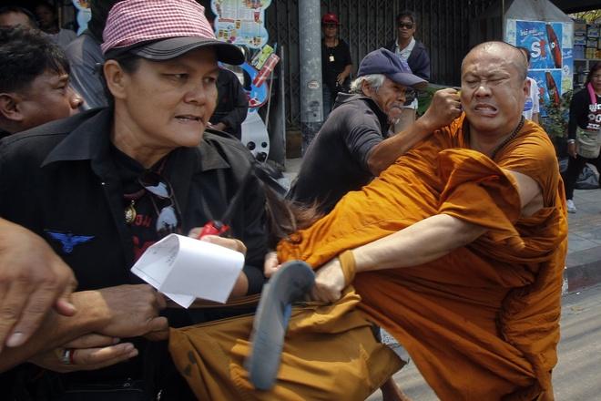 """Nhung buc anh khong the quen trong nam 2014 hinh anh 4 Các thành viên của phong trào """"Áo đỏ"""" ủng hộ chính phủ Thái Lan tấn công một nhà sư bên ngoài văn phòng của Ủy ban chống tham nhũng tại ngoại ô thủ đô Bangkok, hồi tháng 3. Sau nhiều tháng bất ổn chính trị, quân đội Hoàng gia Thái Lan tiến hành cuộc đảo chính, lật đổ chính phủ và Thủ tướng Yingluck Shinawatra vào tháng 5."""