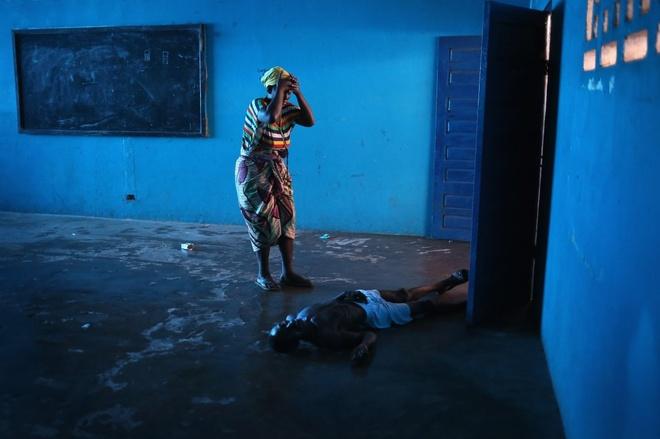 Người phụ nữ Liberia đau khổ khi chứng kiến cảnh người chồng qua đời vì nhiễm virus Ebola. Đại dịch Ebola ở Tây Phi bắt đầu vào tháng 12/2013, nhưng mãi tháng 7 và 8, người ta mới thực sự chú ý tới mức độ nguy hiểm mà nó gây ra sau khi Liberia đóng cửa biên giới và thiết lập các khu vực kiểm dịch.