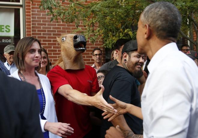 Nguoi Viet cho do cong kenh vao top anh ky thu nhat nam 2014 hinh anh 10 Một người dân đeo mặt nạ đầu ngựa và bắt tay với Tổng thống Barack Obama khi nhà lãnh đạo Mỹ công tác ở thành phố Denver, bang Colorado vào ngày 8/7. Ảnh: Reuters
