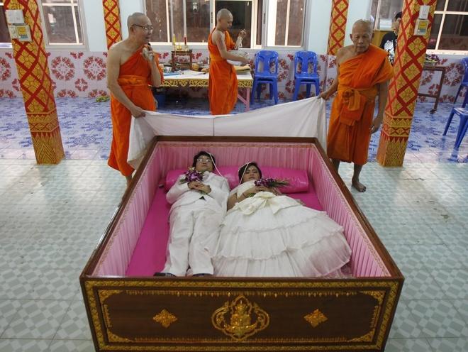 Nguoi Viet cho do cong kenh vao top anh ky thu nhat nam 2014 hinh anh 3 Chú rể Tanapatpurin Samangnitit, 40 tuổi, và cô dâu Sunantaluk Kongkoon, 26 tuổi, nằm trong một quan tài trong lễ cưới của họ ở ngoại ô Bangkok vào ngày 14/2. Cặp đôi tin rằng việc nằm trong quan tài sẽ xua tan mọi xui xẻo và mang lại những điều may mắn trong cuộc sống. Ảnh: Reuters