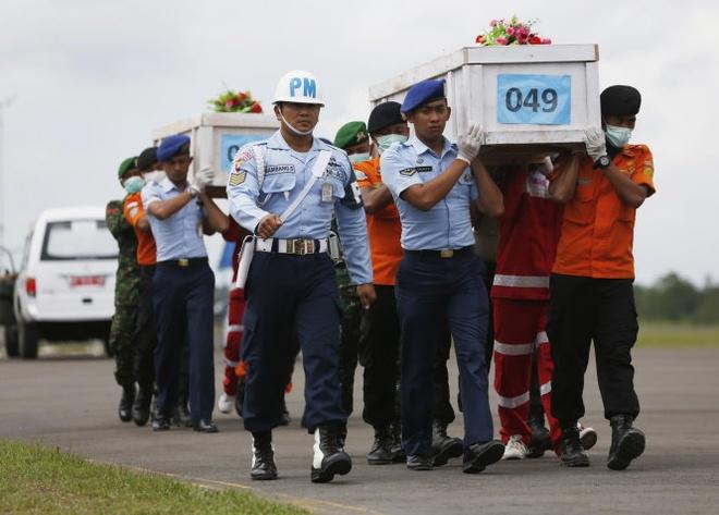 May bay AirAsia bay cao bat thuong do gio hinh anh 1 Nhân viên cứu hộ Indonesia khiêng quan tài chứa thi thể hành khách chuyến bay AirAsia QZ8501.  Ảnh: Reuters