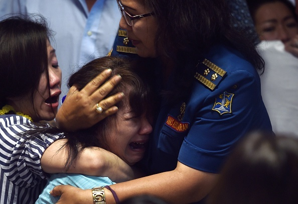 Toan canh mot thang tham kich QZ8501 chan dong the gioi hinh anh 3 Người thân của các nạn nhân trên chuyến bay QZ8501 an ủi nhau sau khi nghe tin dữ. Ảnh: AFP