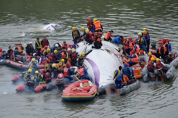 So nguoi chet trong vu may bay TransAsia len den 40 nguoi hinh anh 1 Đội cứu hộ tìm kiếm nạn nhân từ hiện trường máy bay rơi. Ảnh: AFP