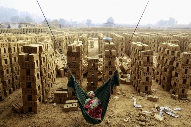 Khoanh khac may bay Dai Loan lao xuong song vao top anh tuan hinh anh 4 Một bé trai ngủ say trên chiếc võng tại một lò gạch ở ngoại ô thủ đô Yangon của Myanmar, trong khi mẹ em đang làm việc.