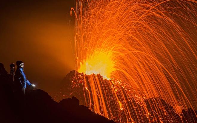 Một người leo núi đang quan sát cảnh núi lửa Piton de la Fournaise phun trào ở đảo La Reunion, Ấn Độ Dương. Sau khi ngủ yên trong 3 năm qua, đây là lần thứ hai trong năm 2015, núi lửa Piton de la Fournaise thức giấc.  Ảnh: AP