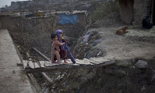 Bé gái dắt cậu em trai qua cầu gỗ xập xệ ở một khu ổ chuột của người tị nạn Afghanistan, ngoại ô thủ đô Islamabad, Pakistan.