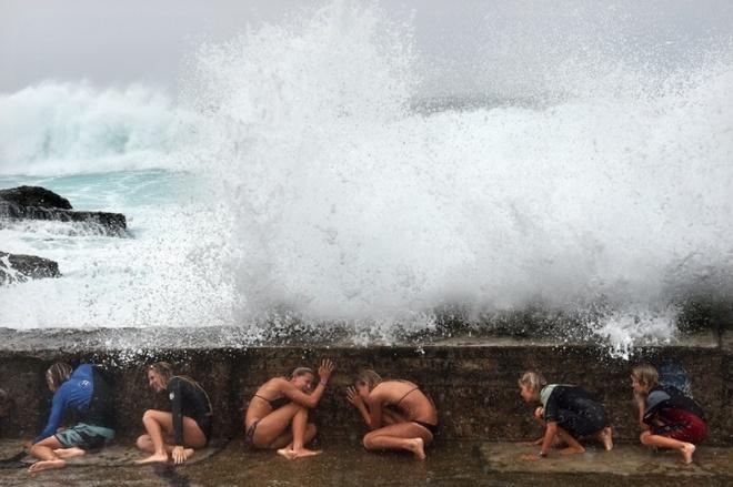 Các cô gái núp dưới một con đê của Bờ Biển Vàng khi sóng dâng cao do cơn bão nhiệt đới Marica đổ bộ vào đông bắc Australia hôm 20/2.