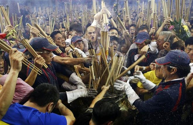 Người dân Singapore chen nhau để thắp những nén hương khổng lồ vào lư hương tại chùa Kwan Im Thong Hood trong thời khắc giao thừa Tết âm lịch. Họ mong muốn là người đầu tiên thắp hương để có một sự khởi đầu tốt đẹp trong năm Ất Mùi.