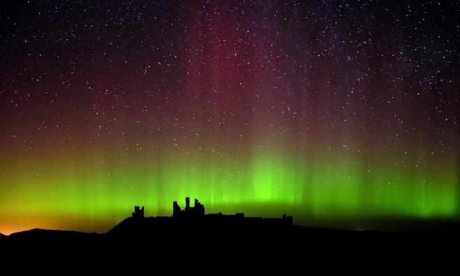 Cực quang phát sáng trên vùng trời lâu đài Dunstanburgh ở Northumberland, Anh.  Ảnh: PA