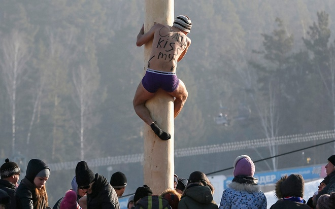Loat anh an tuong nhat tuan (23 -28/2) hinh anh 7 Một người đàn ông leo lên một chiếc cột cao 13 m để giành giải thưởng trong lễ hội tiễn biệt mùa đông Maslenitsa tại khu trượt tuyết Bobrovy Log, ngoại ô Krasnoyarsk. Trong thời gian lễ hội diễn ra, người dân Nga sẽ cùng nhau ăn bánh và khoe sức mạnh của cơ thể.