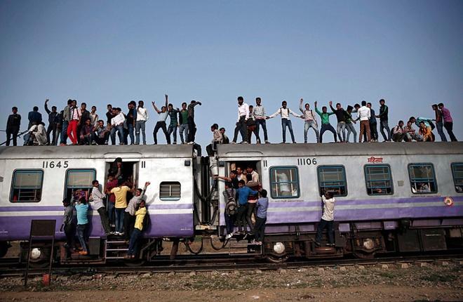 Loat anh an tuong nhat tuan (23 -28/2) hinh anh 3 Nhiều hành khách đứng trên nóc đoàn tàu và bám vào cửa trong một chuyến tàu đông đúc tại ngoại ô thành phố New Delhi. Chính phủ Độ cho biết, trong 5 năm tới, họ sẽ tăng cường đầu tư để nâng cấp và hiện đại hóa mạng lưới đường sắt đang ngày càng xuống cấp.