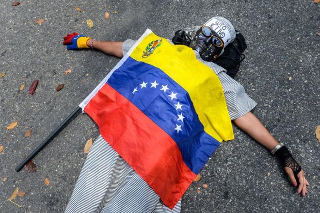 Loat anh an tuong nhat tuan (23 -28/2) hinh anh 1 Một nhà hoạt động thuộc phe đối lập nằm giữa đường để phản đối cái chết của một học sinh 14 tuổi trong một cuộc biểu tình chống khủng hoảng kinh tế ở bang Tachira, thủ đô Caracas của Venezuela, hôm 24/2. Công tố viên Venezuela cho biết họ sẽ buộc tội một cảnh sát liên quan đến cái chết của thiếu niên này.