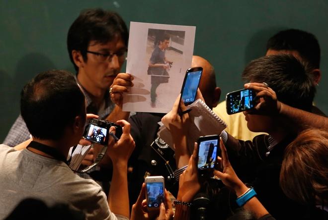 Toan canh 1 nam mat tich bi an cua chuyen bay MH370 hinh anh 11 Một nhà báo cầm ảnh của một hành khách mà cảnh sát Malaysia khẳng định đã dùng hộ chiếu giả để bước lên chuyến bay MH370. Khi đó, giới chức Malaysia không loại trừ khả năng máy bay bị không tặc. Ảnh: Reuters