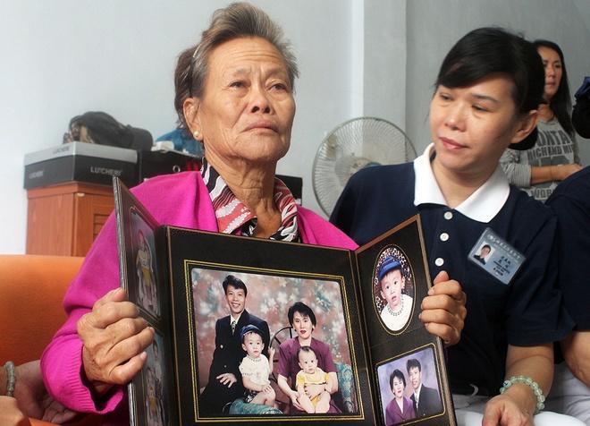 Toan canh 1 nam mat tich bi an cua chuyen bay MH370 hinh anh 5 Bà Suharni (người Indonesia) cầm ảnh con trai và vợ của anh. Con trai và con dâu của bà đều là hành khách trên MH370. Ảnh: AFP
